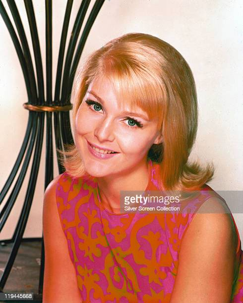 Carol Lynley US actress wearing a pinkandorange sleeveless top smiling in a studio portrait 1970