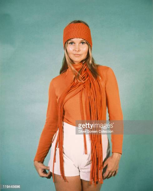 Carol Lynley US actress wearing white shorts an orange polo neck jumper an orange headband and an orange fringed scarf in a publicity portrait...