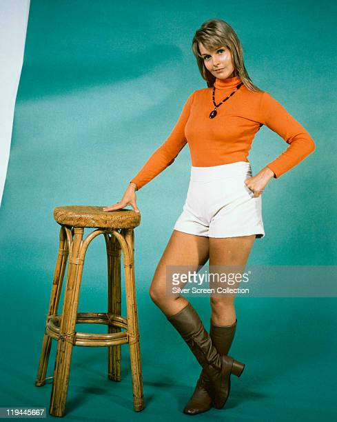 Carol Lynley US actress with one hand leaning on a stool as she poses wearing white shorts an orange polo neck jumper and brown boots in a publicity...