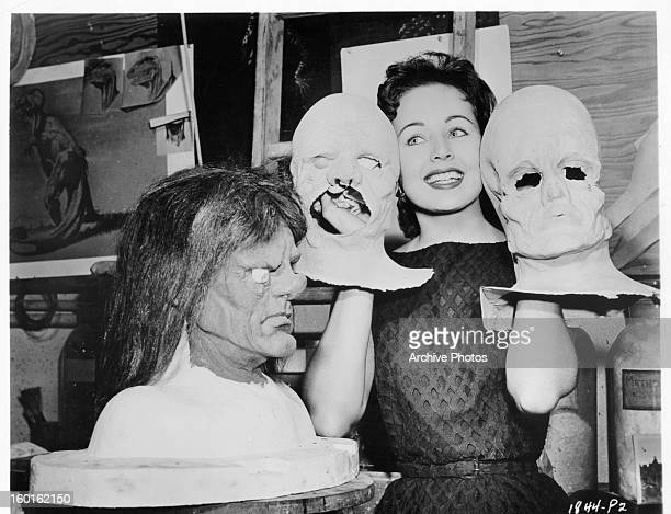 Carol Morris poses with latex faces in between scenes from the film 'Man Of A Thousand Faces', 1957.