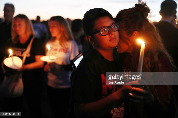 Carol Ortez hugs her son Aaron Ortez as he holds a candle during a memorial service at Pine Trails Park for the victims of the mass shooting at...