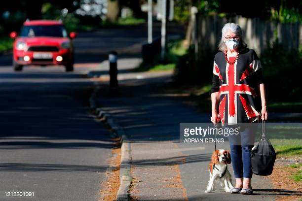Carol Service wearing a protective face mask, walks her cavalier king charles spaniel on the 75th anniversary of VE Day , the end of the Second World...