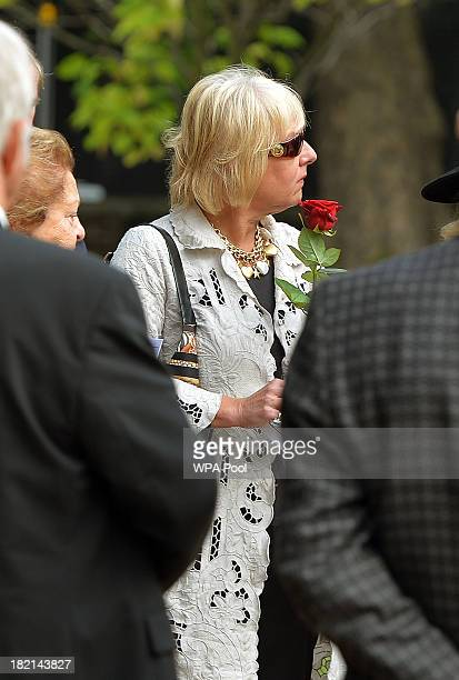 Carol Thatcher holds a red rose before placing it with the ashes of her mother former British Prime Minister Baroness Margaret Thatcher as her...