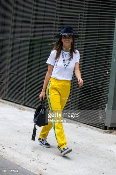 Carola Bernard wears yellow Palm Angels track pants outside the Y/3 show on June 25 2017 in Paris France