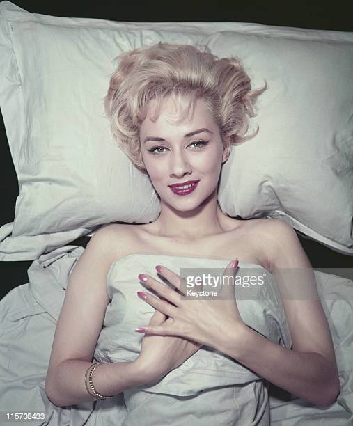 Carole Lesley , British actress, poses seductively in bed, her hands clasped together over the bed clothes, circa 1957.