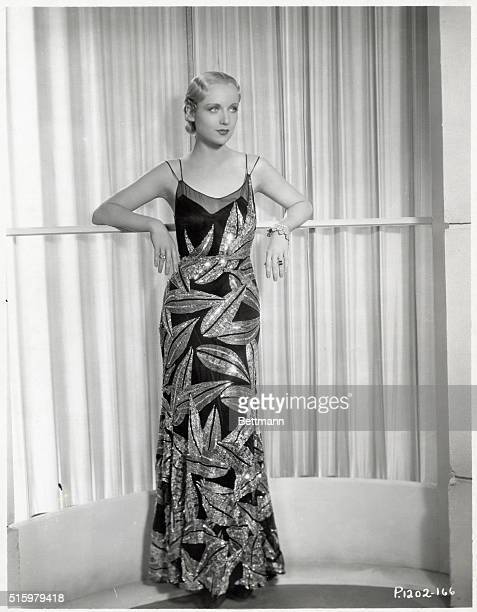 Carole Lombard is shown leaning against a railing Full length photo