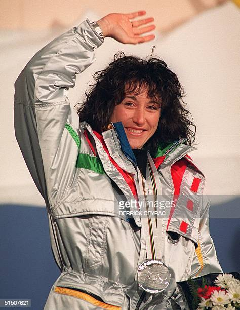 Carole Merle of France smiles on the podium as she waves to the crowd after the medals' ceremony of the women's super giant slalom at the Winter...