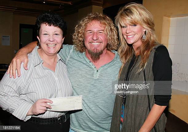 Carole Tremblay of the Los Angeles Regional Foodbank Chickenfoot recording artist Sammy Hagar and wife Kari Hagar pose with a check for $2500...