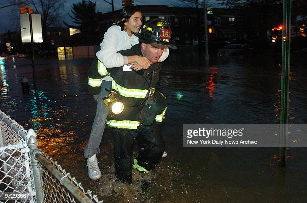 Carolin Bekermann catches a lift from firefighter as water floods a fivesquareblock area in Astoria Queens after construction workers smashed a water...