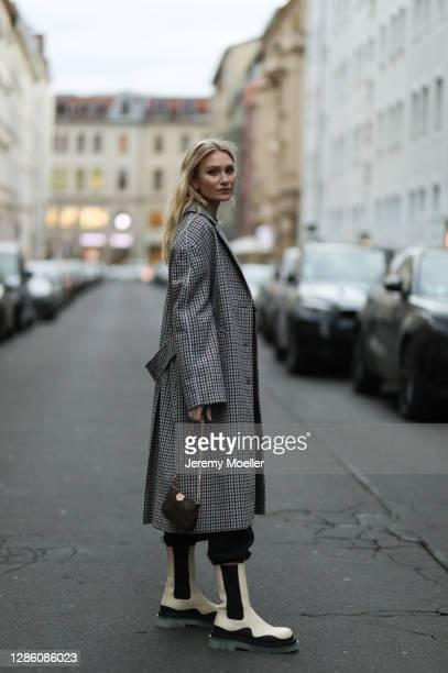 Carolin Niemczyk wearing a Nike trainingsuit, Bottega Veneta boots, Louis Vuitton bag and Zara coat on November 16, 2020 in Berlin, Germany.