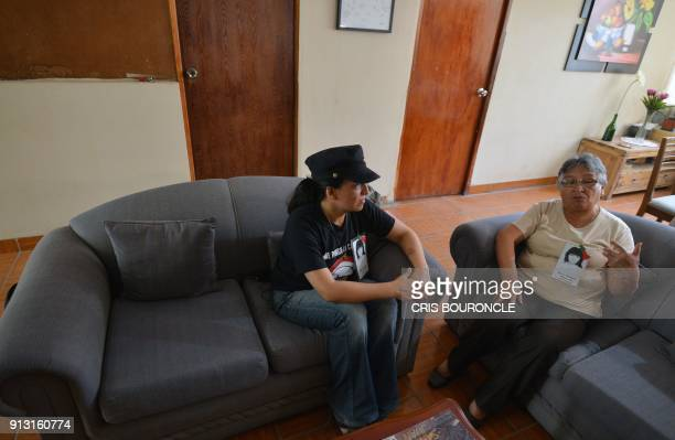 Carolina and her mother Carmen sit in their living room in a middleclass neighbourhood in Lima on January 29 wearing pinned pictures of Carolina's...