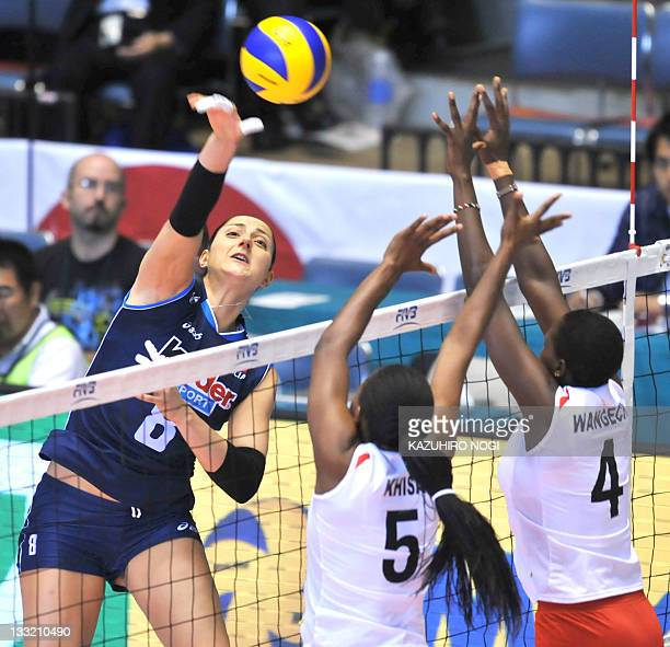 Carolina del Pilar Costagrande of Italy spikes the ball over Kenyan players Diana Khisa and Esther Wangeshi during a match of the World Cup women's...