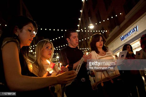 Carolina Fanning second from left of Potomac MD wipes tears away in a prayer circle as Amazing Grace is sung across the street from the Lululemon...