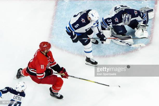 Carolina Hurricanes Center Jordan Staal attempts to track down a loose puck infant of Winnipeg Jets Goalie Connor Hellebuyck during a game between...
