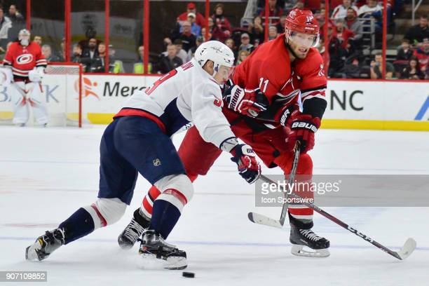 Carolina Hurricanes Center Jordan Staal passes the puck while being grabbed by Washington Capitals Defenceman Dmitry Orlov during a game between the...