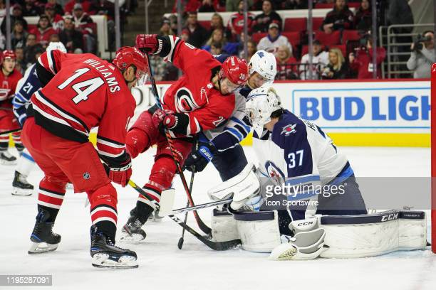 Carolina Hurricanes Center Sebastian Aho and Carolina Hurricanes Right Wing Justin Williams battle for a loose puck in front of Winnipeg Jets Goalie...