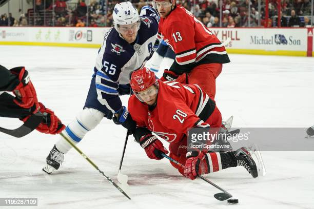 Carolina Hurricanes Center Sebastian Aho falls to the ice after beating Winnipeg Jets Center Mark Scheifele in a faceoff during a game between the...