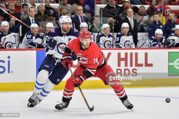 Carolina Hurricanes Defenceman Jaccob Slavin and Winnipeg Jets Right Wing Blake Wheeler chase after a loose puck during a game between the Winnipeg...