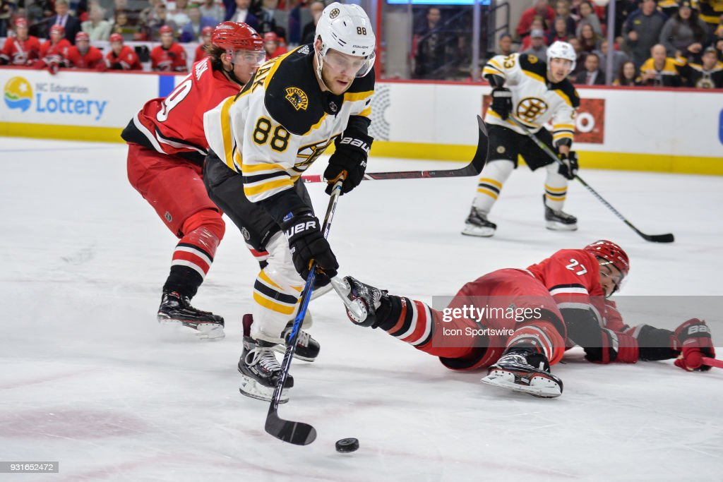 Carolina Hurricanes Defenceman Justin Faulk (27) falls to the ice in front of a charging Boston Bruins Right Wing David Pastrnak (88) during a game between the Carolina Hurricanes and the Boston Bruins at the PNC Arena in Raleigh, NC on March 13, 2018. Boston defeated Carolina 6-4.