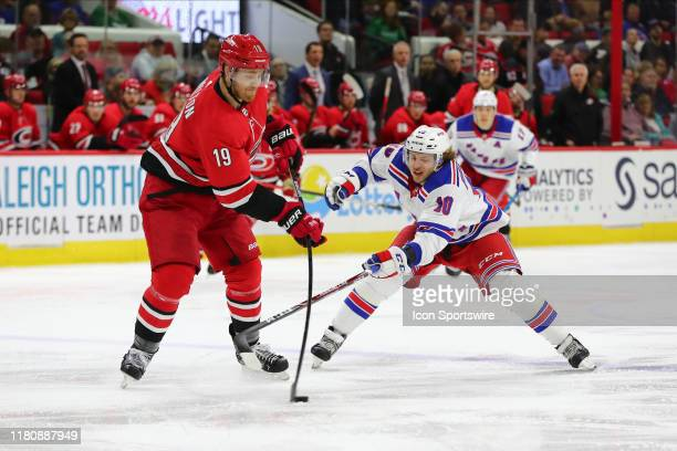 Carolina Hurricanes defenseman Dougie Hamilton passes the puck while New York Rangers center Artemi Panarin goes for it during the 2nd period of the...