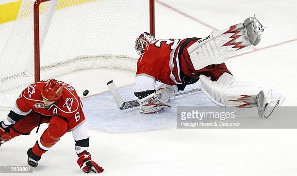 Carolina Hurricanes goalie Cam Ward, right, dives but can't stop a shot by the Washington Capitals' Nicklas Backstrom during third-period action at...