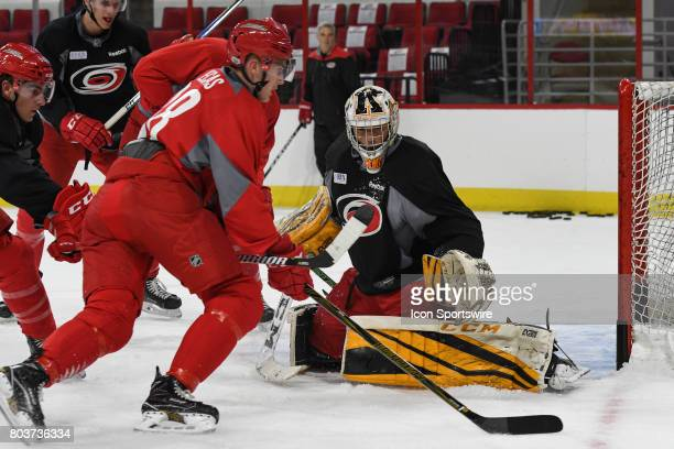 Carolina Hurricanes Goalie Jeremy Helvig watches Carolina Hurricanes Center Martin Necas skate past during the Carolina Hurricanes Development Camp...