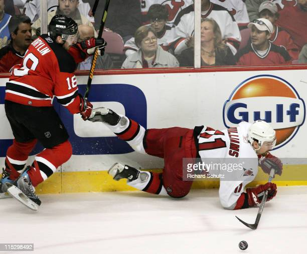 Carolina Hurricanes' Justin Williams flips the puck as he goes down in front of Sergei Brylin of the New Jersey Devils during the first period of...