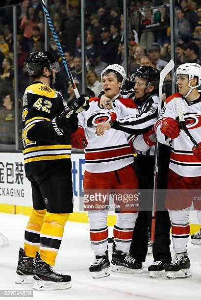 Carolina Hurricanes left wing Jeff Skinner is held back from Boston Bruins center David Backes by linesman Steve Barton during a regular season NHL...
