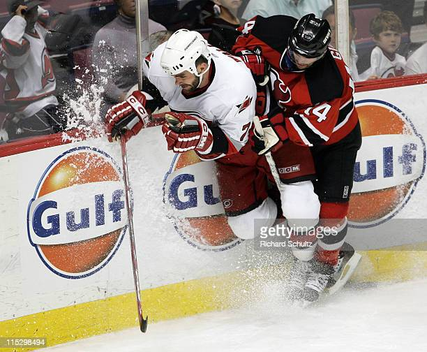 Carolina Hurricanes' Niclas Wallin is checked by Brian Gionta of the New Jersey Devils during the third period of game three in the Eastern...