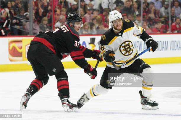 Carolina Hurricanes right wing Andrei Svechnikov cross checks Boston Bruins right wing David Pastrnak after a faceoff during a game between the...