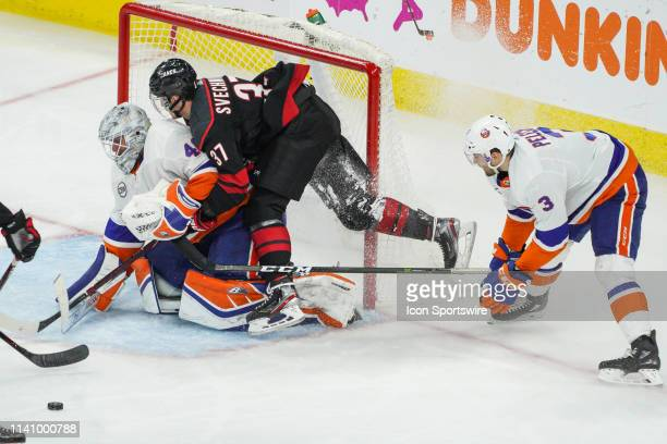 Carolina Hurricanes right wing Andrei Svechnikov tumbles over New York Islanders goaltender Robin Lehner after getting his shot blocked during a game...
