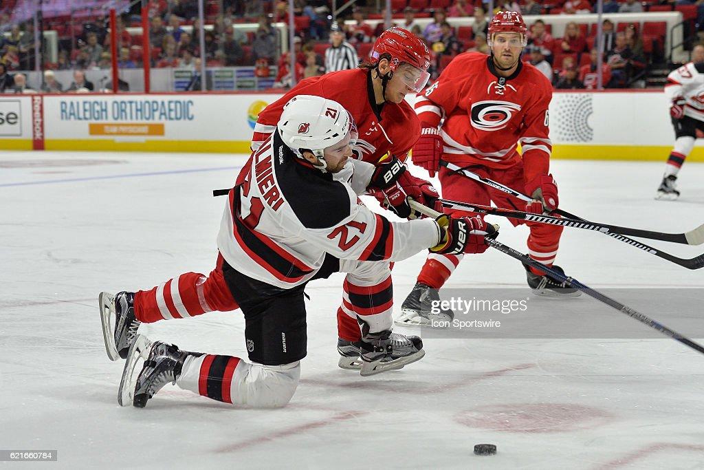 Carolina Hurricanes Winger Sebastian Aho (20) knocks New Jersey Devils  Right Wing Kyle Palmieri c531a8d2f