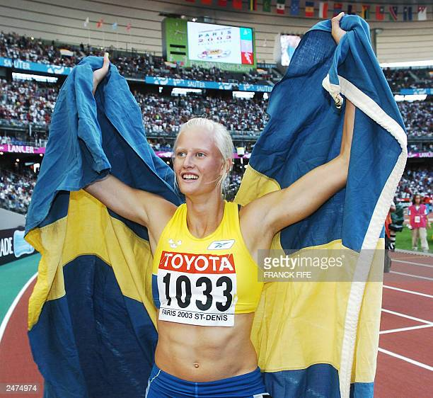 Carolina Kluft of Sweden walks on the track with her national flag after the 800m in the women's heptathlon, 24 August 2003 during the 9th IAAF World...