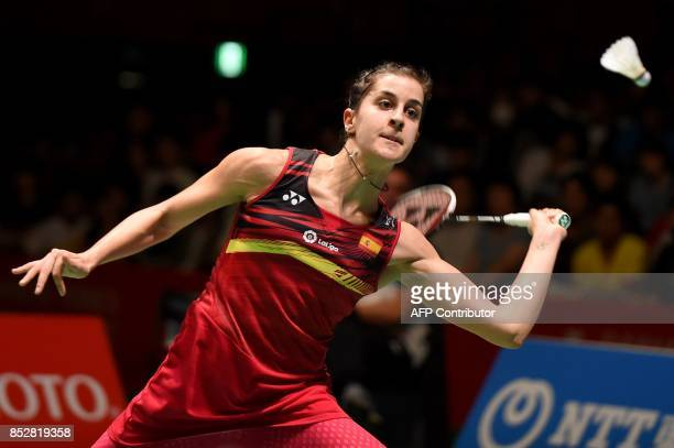 Carolina Marin of Spain hits a return against China's He Bingjiao during the women's singles final match at the Japan Open Badminton Championships in...