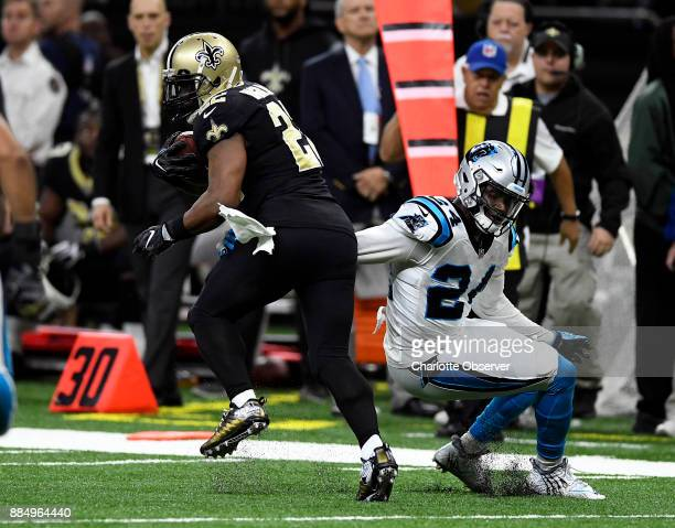 Carolina Panthers cornerback James Bradberry reaches back to try to tackle New Orleans Saints running back Mark Ingram during the first half on...