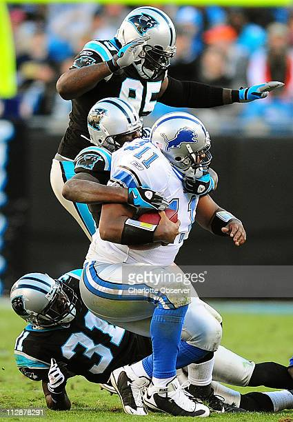 Carolina Panthers cornerback Richard Marshall linebacker Thomas Davis and defensive end Charles Johnson pressure Detroit Lions quarterback Daunte...