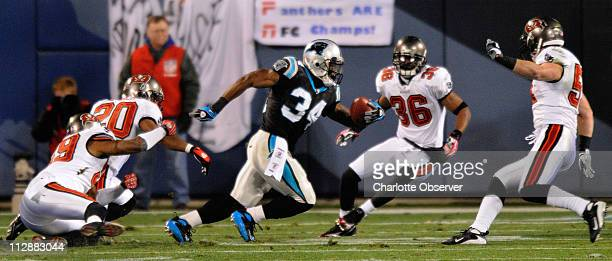 Carolina Panthers' DeAngelo Williams tries to evade the Tampa Bay Buccaneers' defense in the first quarter at the Bank of America Stadium in...