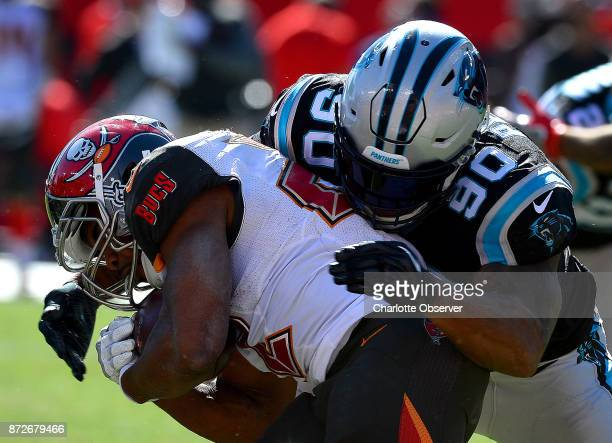 Carolina Panthers defensive end Julius Peppers right makes the tackle on Tampa Bay Buccaneers running back Doug Martin on October 29 at Raymond James...