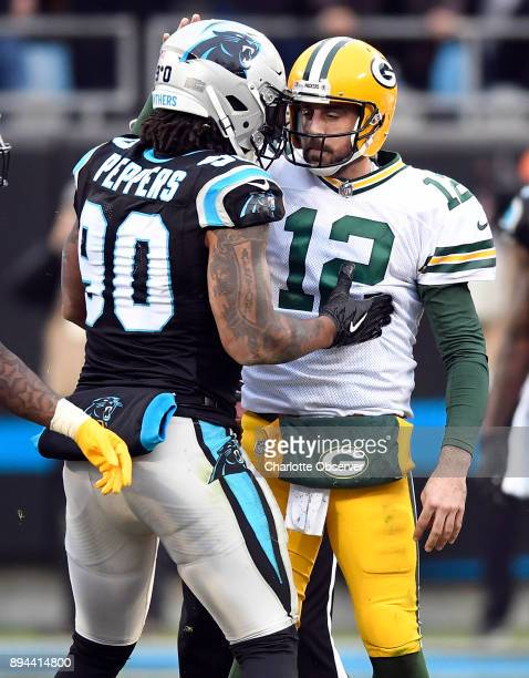 Carolina Panthers defensive end Julius Peppers talks with Green Bay Packers quarterback Aaron Rodgers after helping sack him in the second half on...