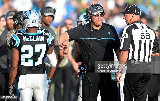 Carolina Panthers head coach Ron Rivera congratulates cornerback Robert McClain as he talks with line judge Tom Stephan while playing against the Los...
