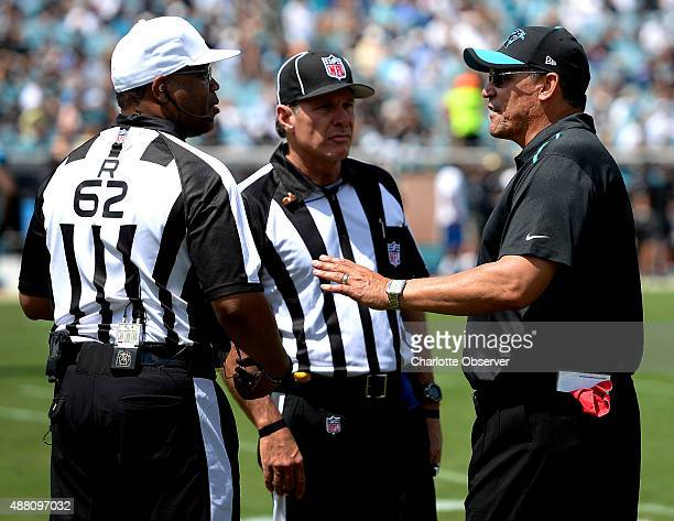 Carolina Panthers head coach Ron Rivera right talks with referee Ronald Torbert left and side judge Scott Edwards middle during the first quarter at...