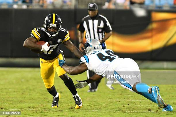Carolina Panthers linebacker Antwione Williams leaps at Pittsburgh Steelers wide receiver Eli Rogers to attempt a tackle during the preseason game...