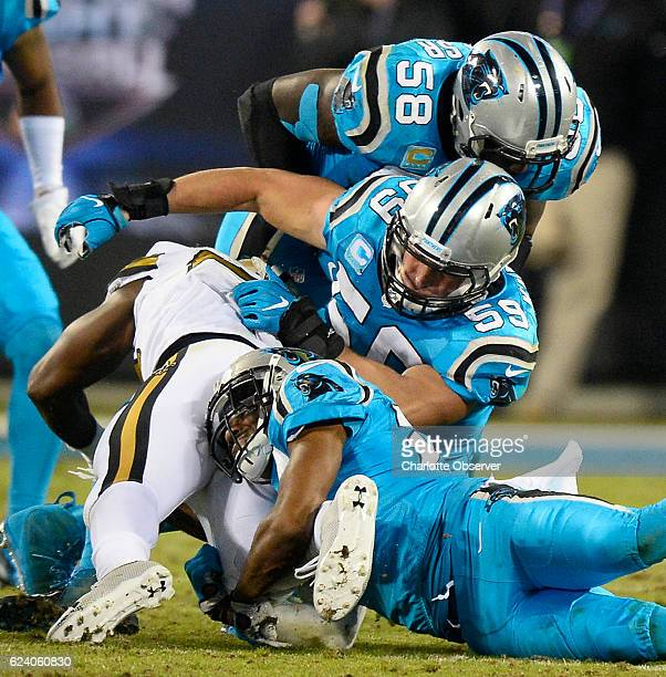 Carolina Panthers middle linebacker Luke Kuechly is injured as he combines to tackle New Orleans Saints running back Tim Hightower along with...