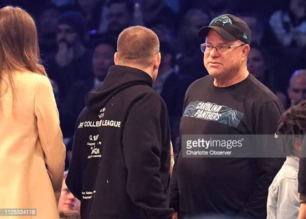 Carolina Panthers owner David Tepper right talks with a passerby along courtside during the NBA AllStar Saturday Night festivities at Spectrum Center...