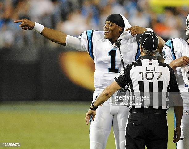 Carolina Panthers quarterback Cam Newton jokes with line judge Ron Marinucci during a timeout in the second quarter against the Chicago Bears during...