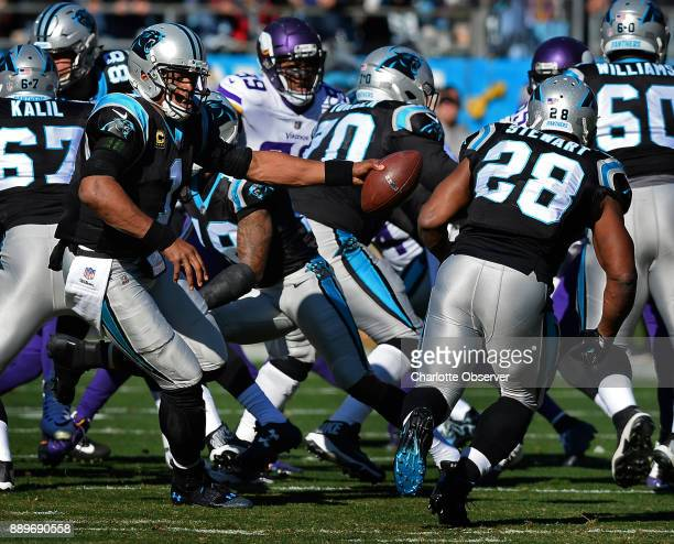 Carolina Panthers quarterback Cam Newton left turns to hand the ball off to running back Jonathan Stewart as the Minnesota Vikings defense rushes...