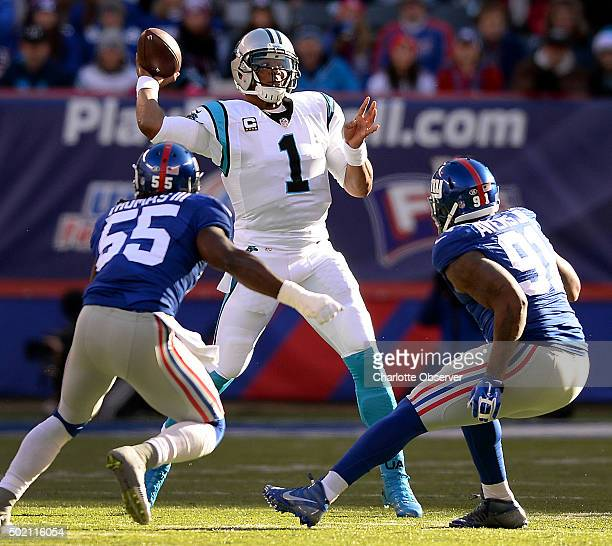 Carolina Panthers quarterback Cam Newton releases a pass over New York Giants linebacker J.T. Thomas III, left, and defensive end Robert Ayers Jr.,...