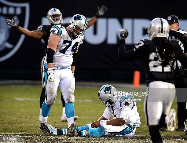 Carolina Panthers quarterback Cam Newton sits on the turf dejected after having the ball stripped from his hand by Oakland Raiders defensive end...