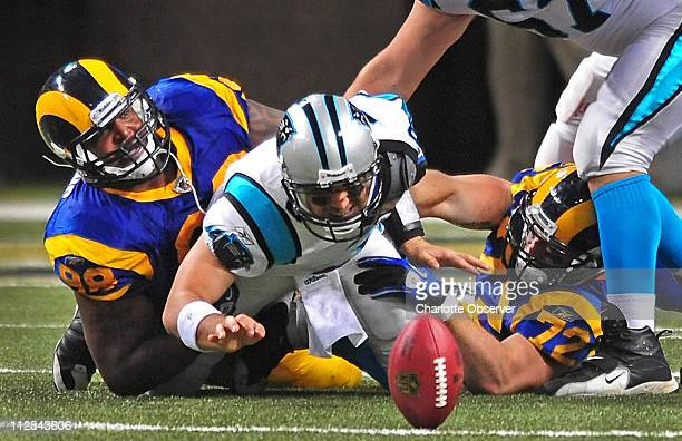 Carolina Panthers quarterback Matt Moore fumbles the football as he is hit by St. Louis Rams defensive tackle Fred Robbins and defensive end Chris...