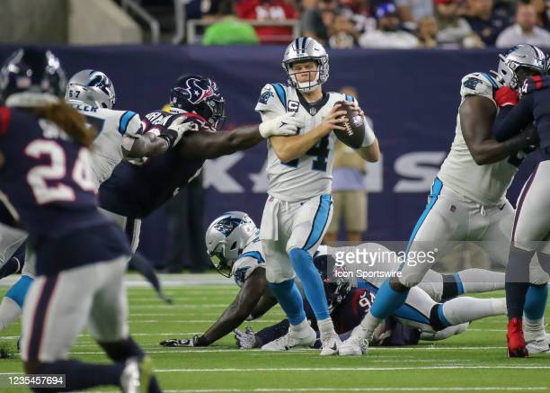 Carolina Panthers quarterback Sam Darnold evades a tackle in the third quarter during the football game between the Carolina Panthers and Houston...